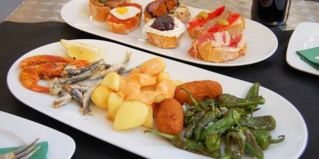 Tow plates of assorted tapas, with croquettes, mini-fish, and lemon.