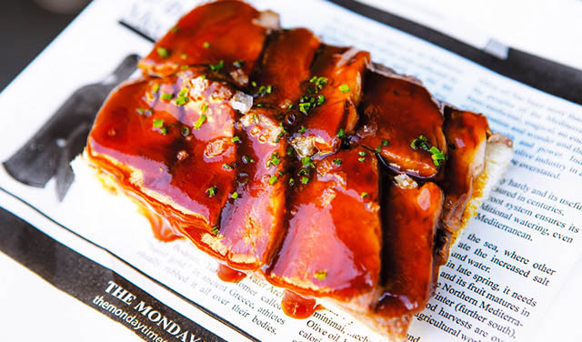 A rack of pork ribs slathered in a meaty-looking sauce.