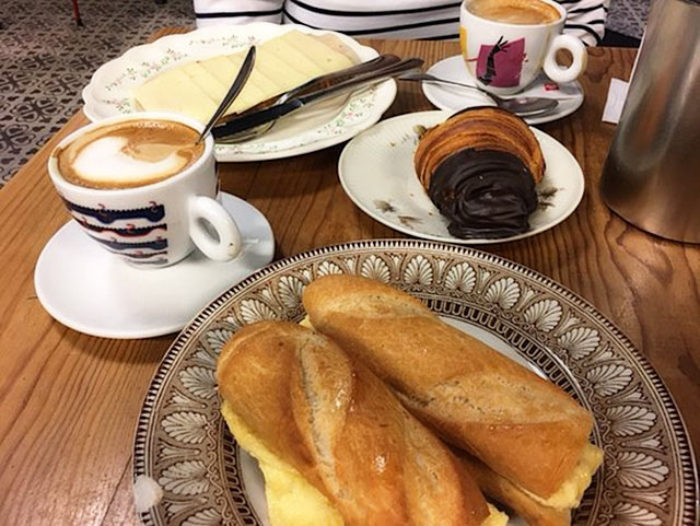 The famous Puiggros pa de forn breakfast is shown with coffee, a chocolate croissant, and a crusty French bread sandwich.