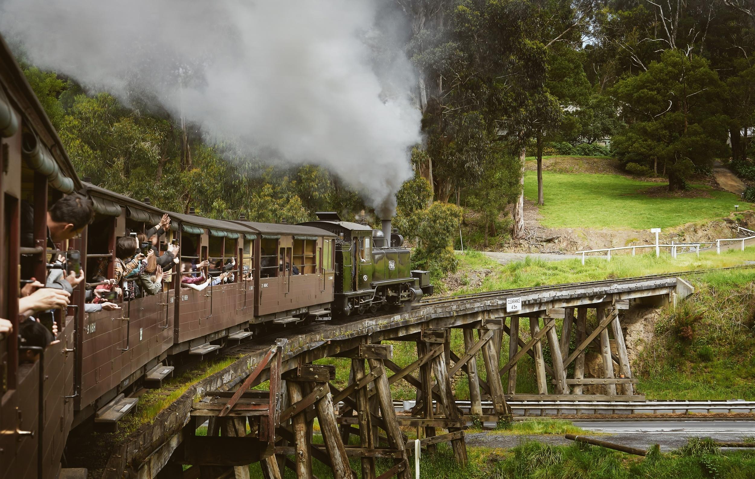 Vintage steam train crossing a wood bridge