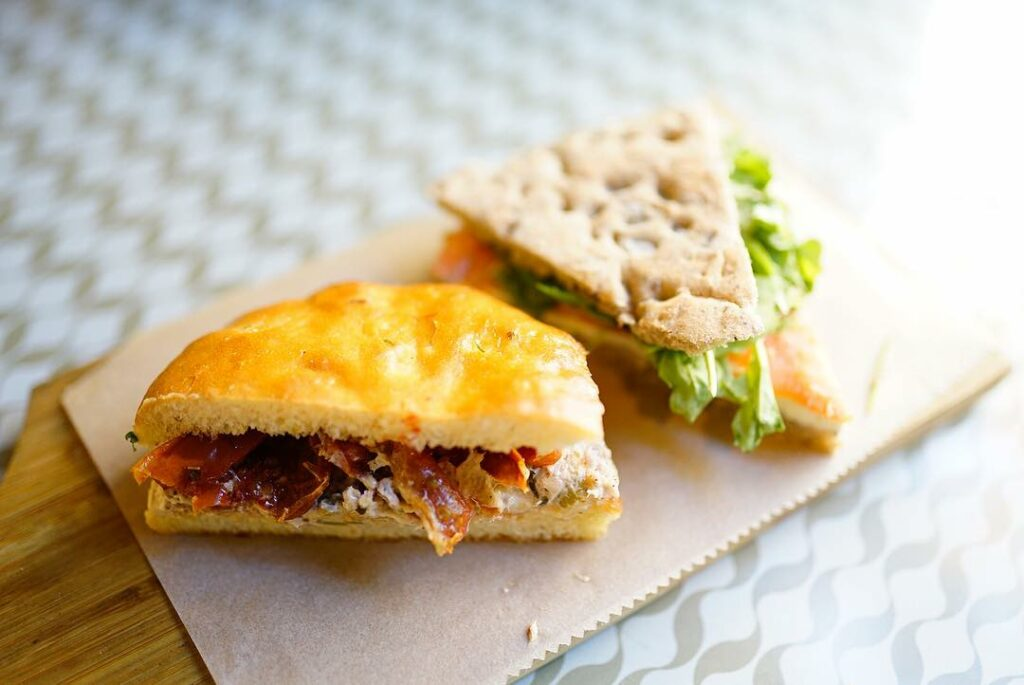 Two types of focaccia bread sandwich. One, the superior option, with bacon. The other appears to have some form of plant in it.