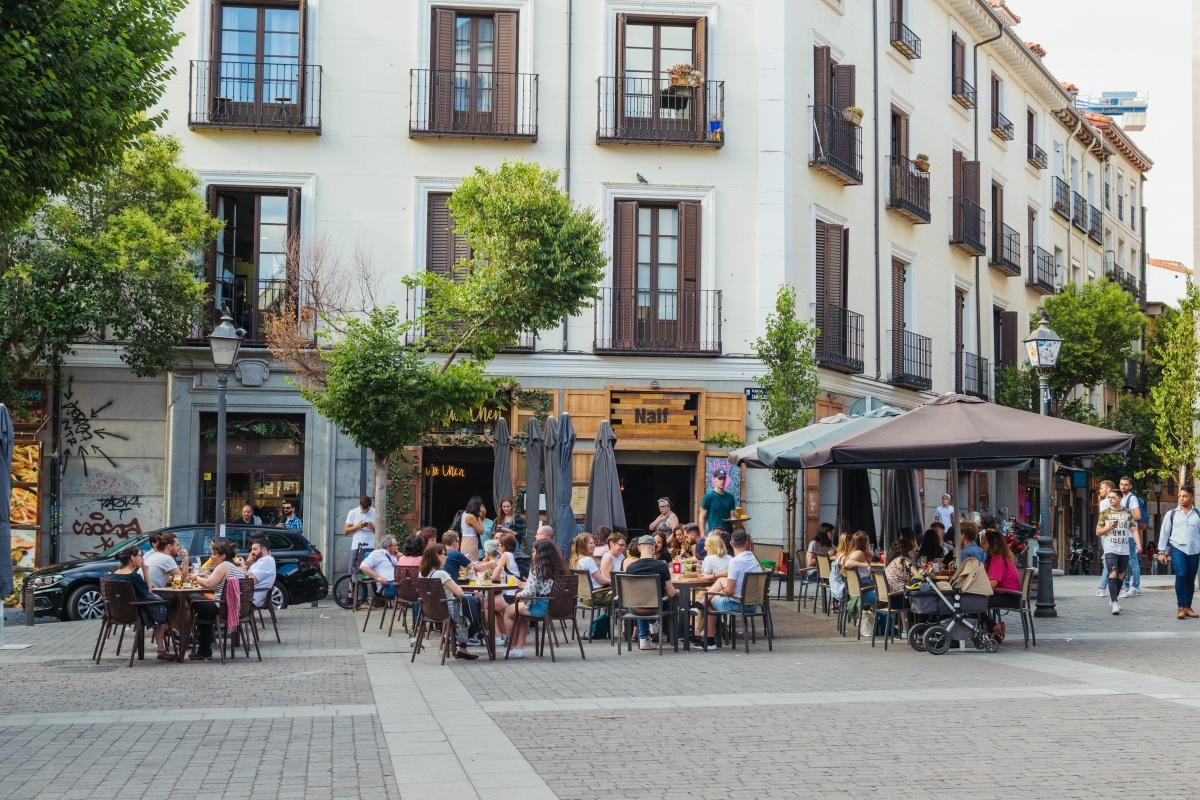 Santa Barbara Square in Malasaña, University District. traditional terrace and people gathering at sunset.