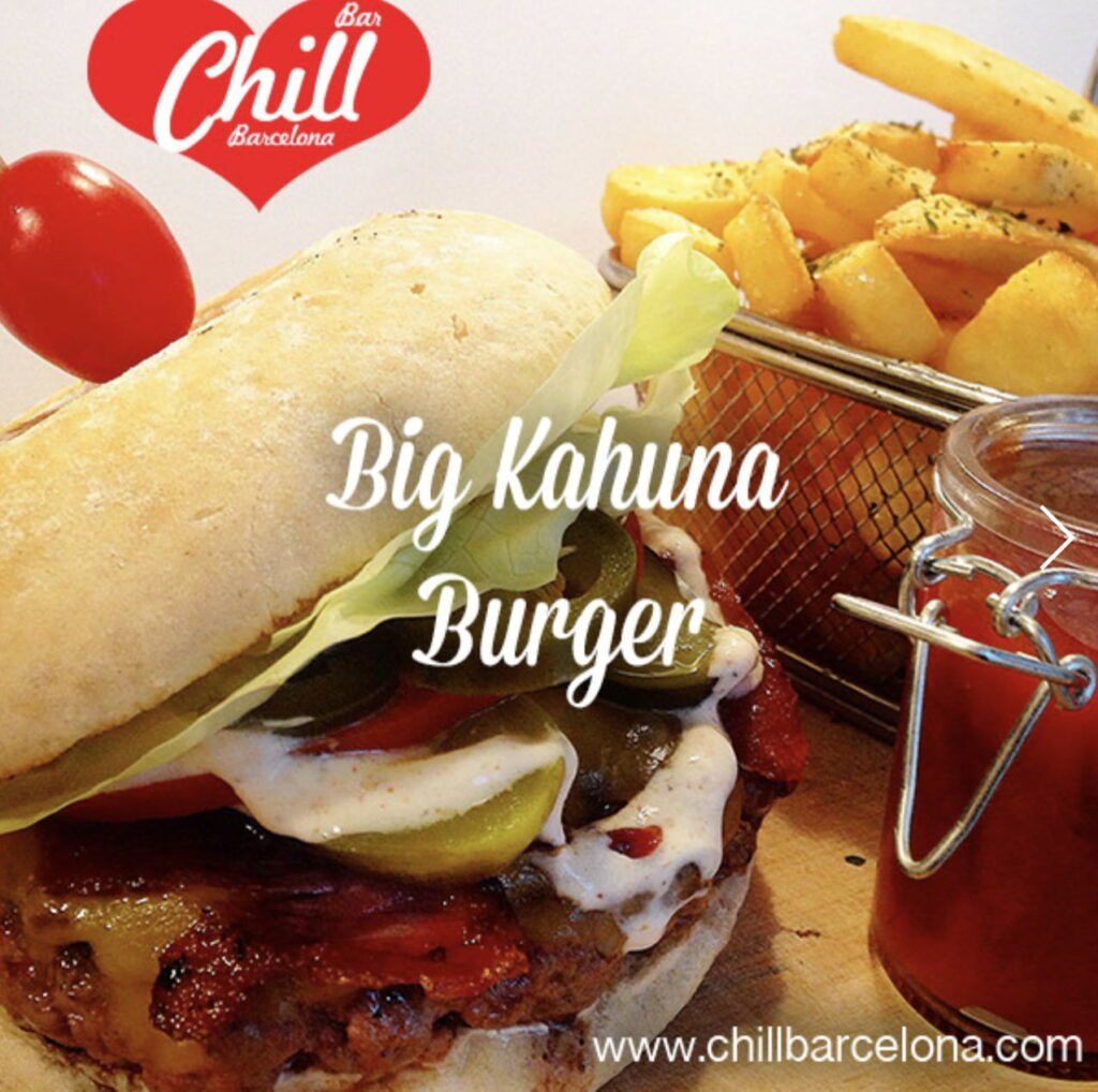 A large burger overflows with pickles and sauce beside a basket of fries.