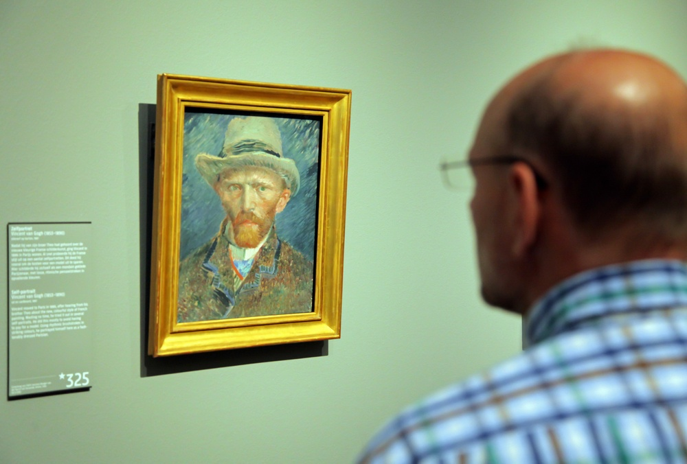 A man looks at van Gogh's self=portrait in the Rijksmuseum.