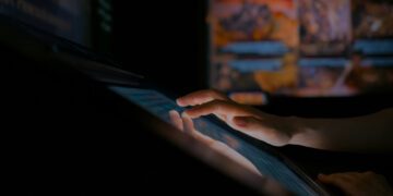 Woman using interactive touchscreen display in modern historical museum. Evening time, lowlight