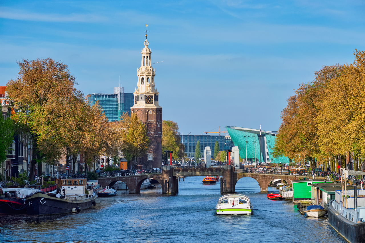 Canal View with bridge and church tower, NEMO is visible through the trees on a sunny autumn day.