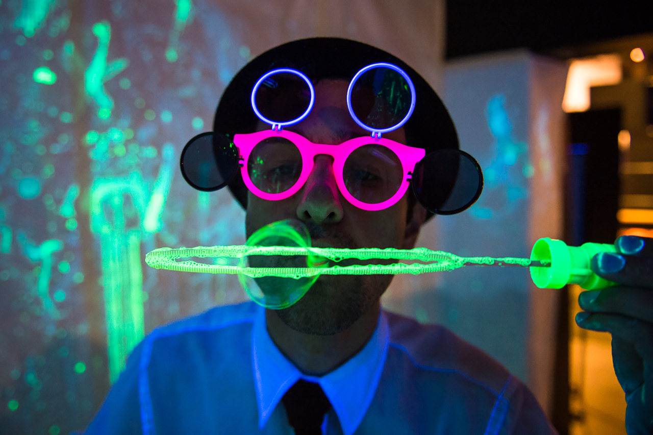 Man wearing colourful glasses blowing bubbles in fluorescent light