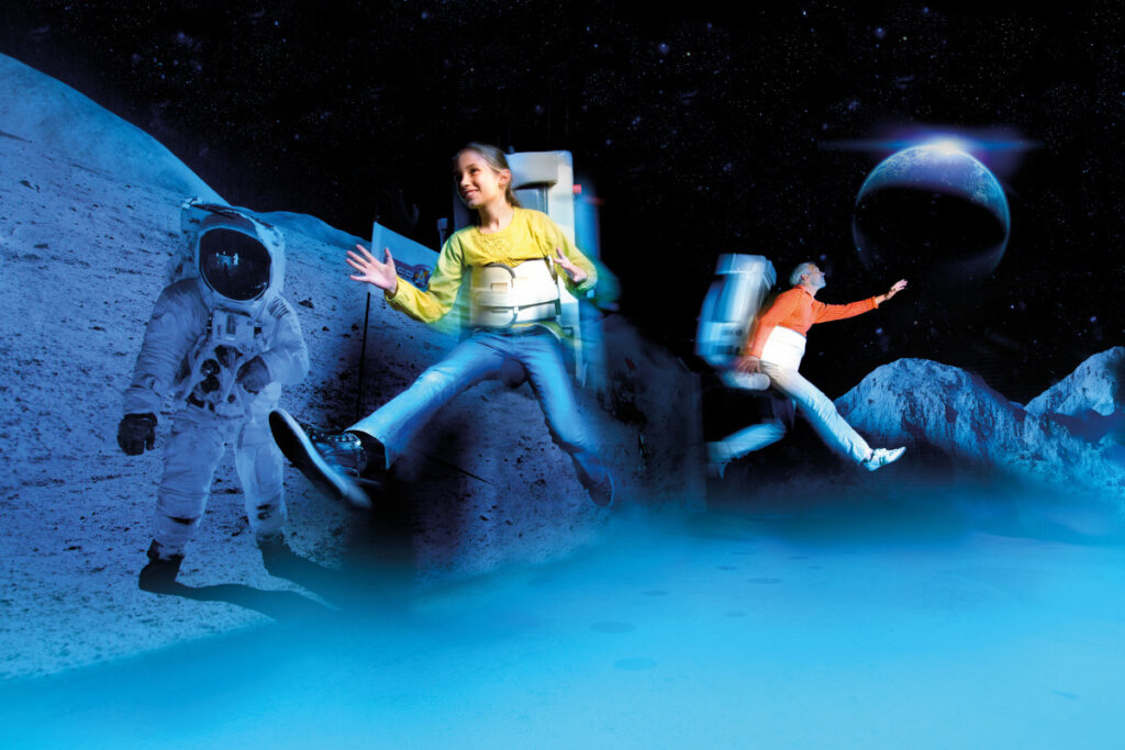 Smiling girl and older man are floating above the ground with space gear on in a moon landscape