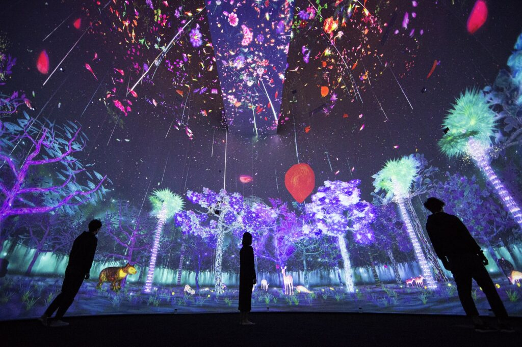 People standing in a room surrounded by a projection of a forest illustration with animals in many colours