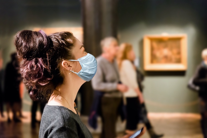 A women visiting one of the museums in the hague wearing a face mask.