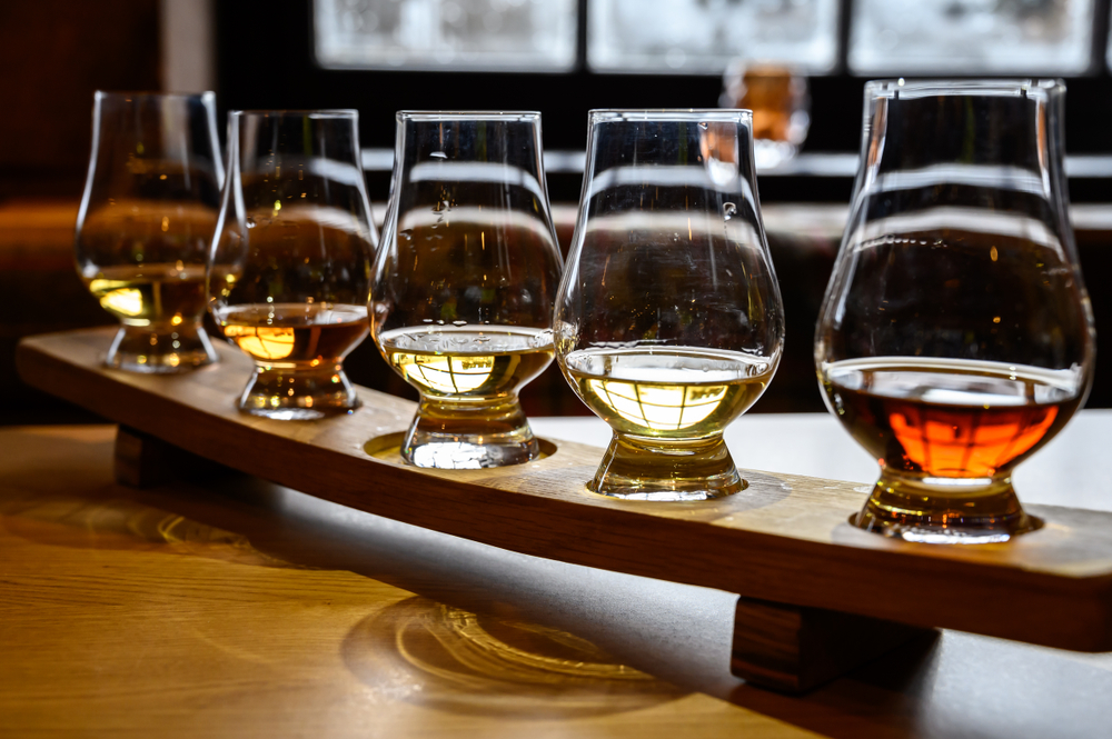 A typical Scotch tasting board with five different whiskies.