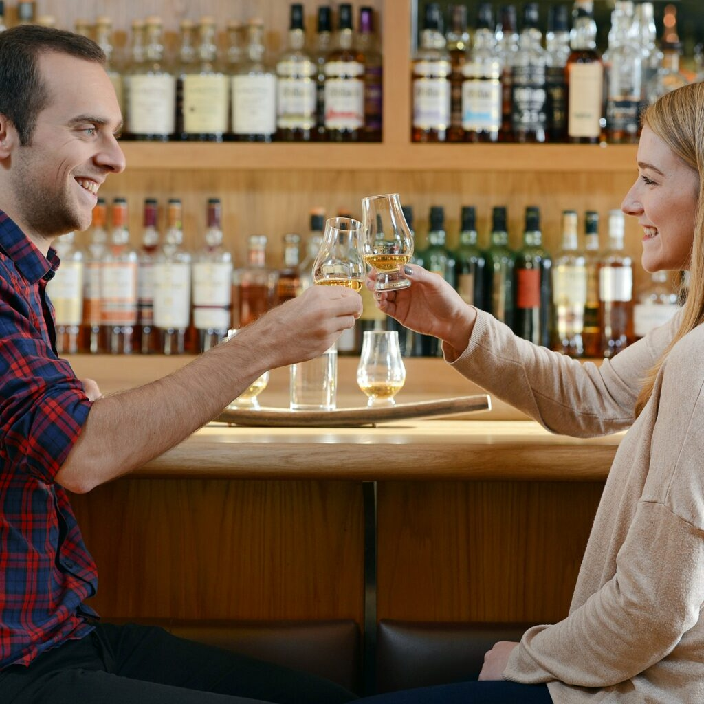 Two people clink whisky glasses at a Scotch tasting.