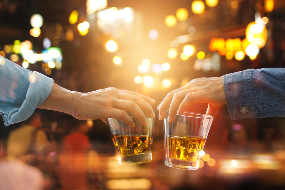 Two people cheers their whisky glasses.
