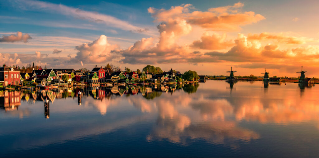 Golden hour at Zaanse Schans. Colourful houses by the waterside. Windmills in the distance