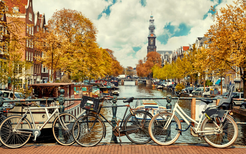 Autumn view from a bridge over the canal. Parked bikes in the foreground, the Westerkerk in the background.