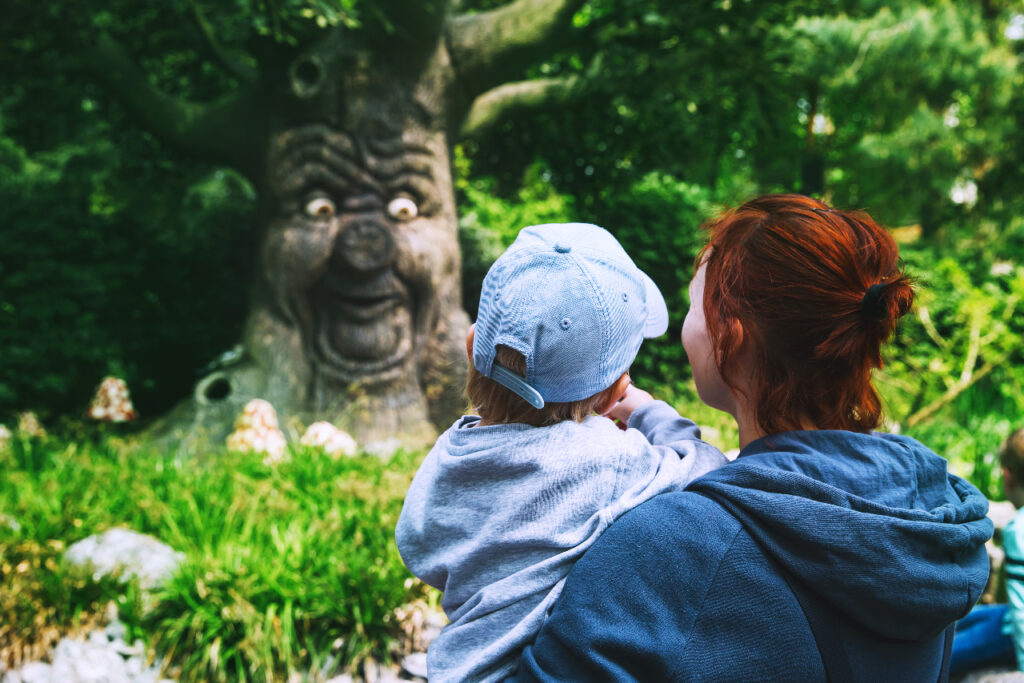 Image of woman and child looking at a tree that has a surprised face.