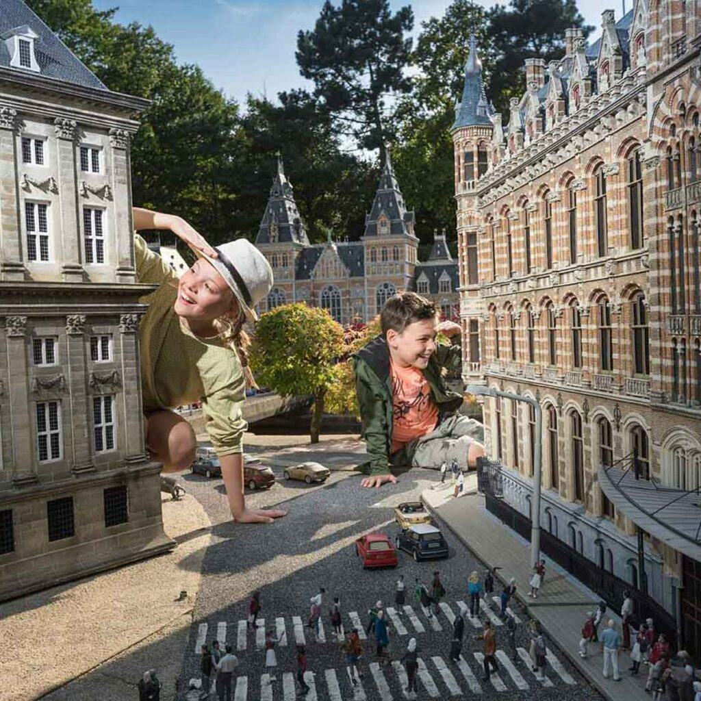 Two children sitting down between two famous Dutch buildings. The kids are very big compared to their surroundings.