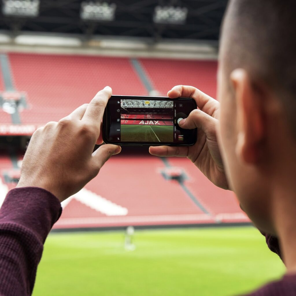 Man holding phone taking a picture of the AJAX logo in the Johan Cruijff ArenA