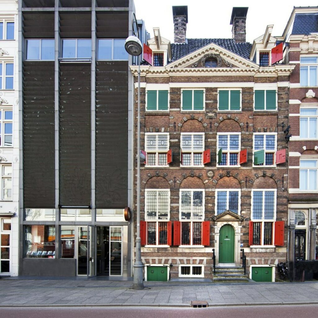 The outside of the Rembrandt house. Old buidling with green and red window shutters