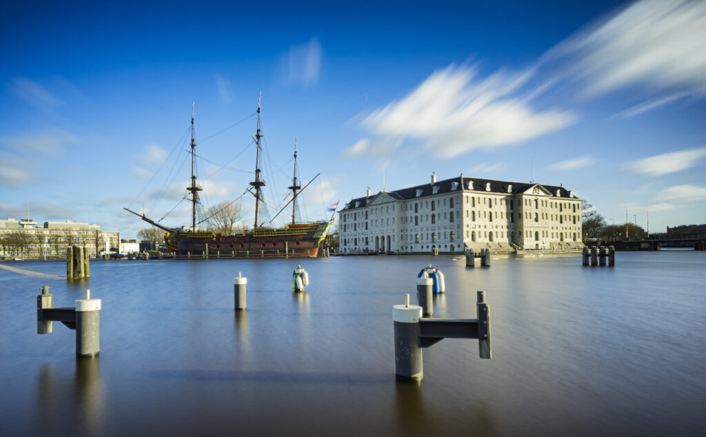 View of the outside of the Scheepvaartmuseum by the water and old VOC ship lying next to it.