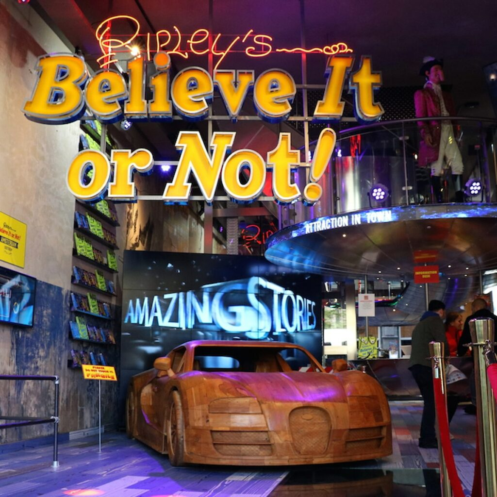 """The Ripley's Hallway. Wooden car in foreground and big screen saying """"Amazing Stories"""" behind it."""