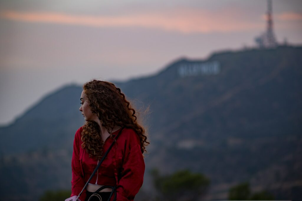 Woman sitting beneath the Hollywood Sign
