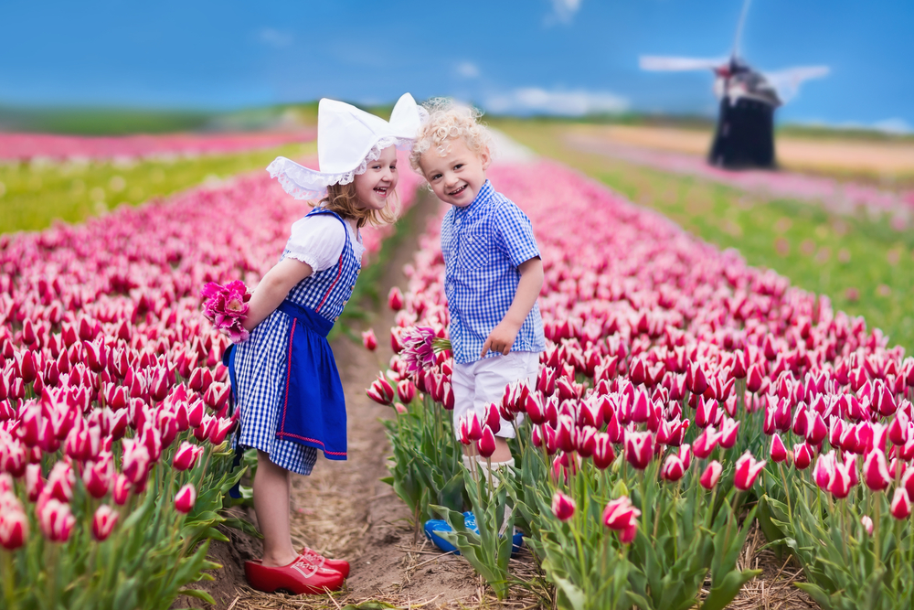 Two young kids standing in the middle of  a flower field at Keukenhof 2021, dressed in typical old Dutch attire