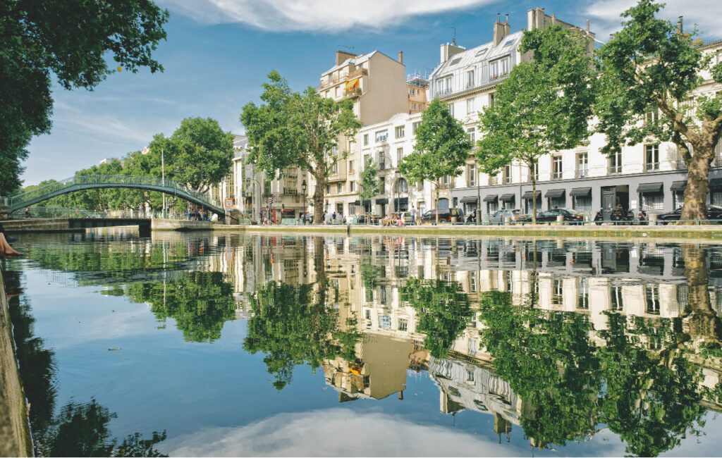 River side view with Parisian buildings on the other side and green trees reflected in the water