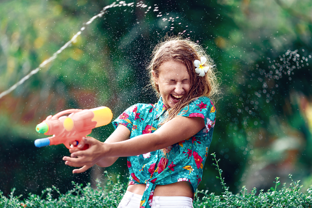 A picture of a young woman with a water pistol possibly partaking in the Polish Easter tradition known as 'Wet Monday'.