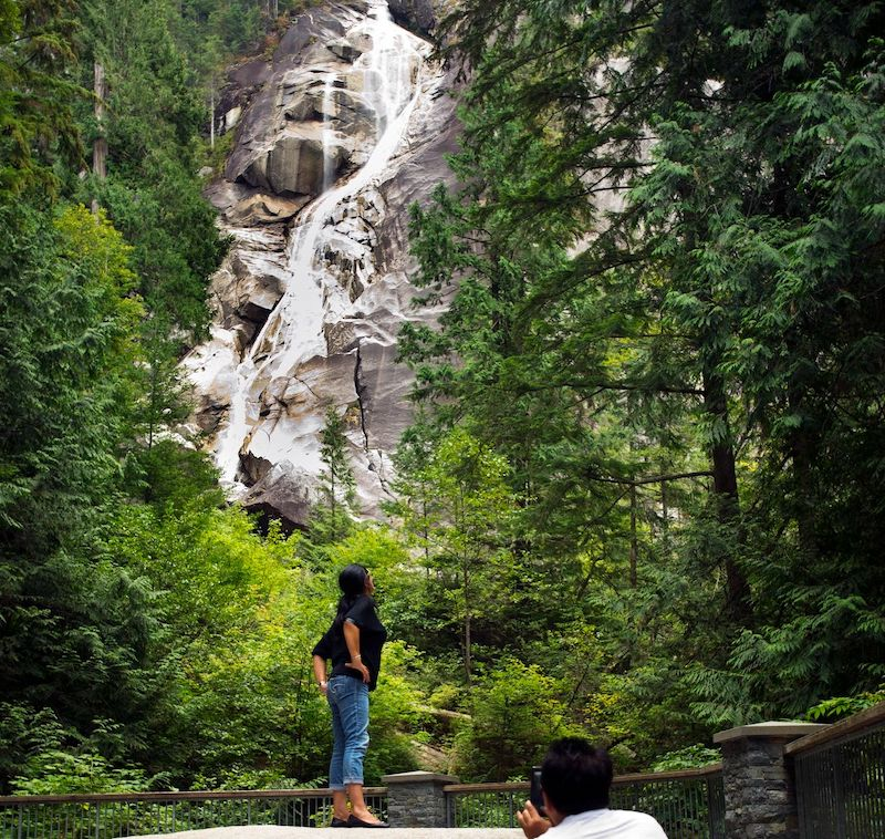 Woman looks up at Shannon Falls