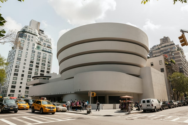 The exterior of New York's The Guggenheim with yellow cabs outside