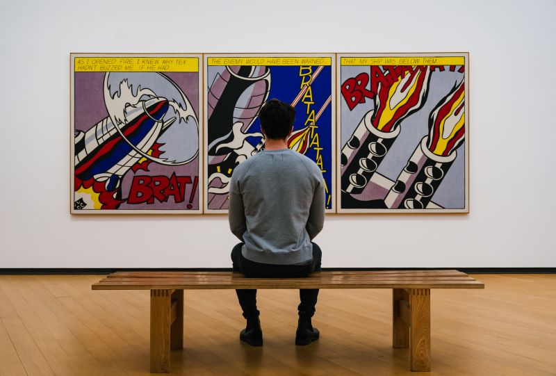 Man seated in front of Roy Lichtenstein's As I Opened Fire