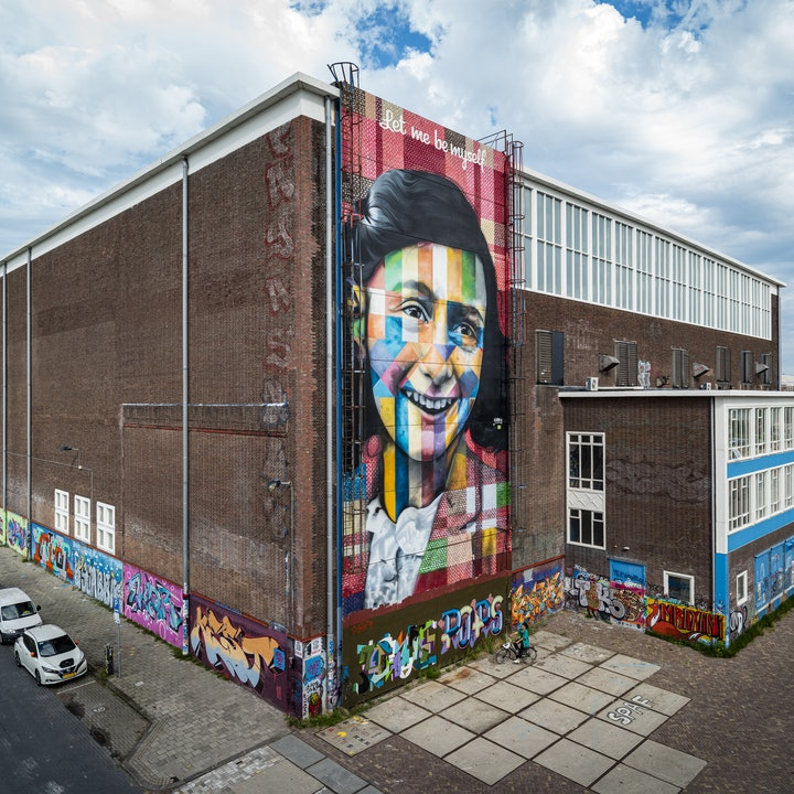 Colourful street art painting of Anne Frank on the side of a warehouse