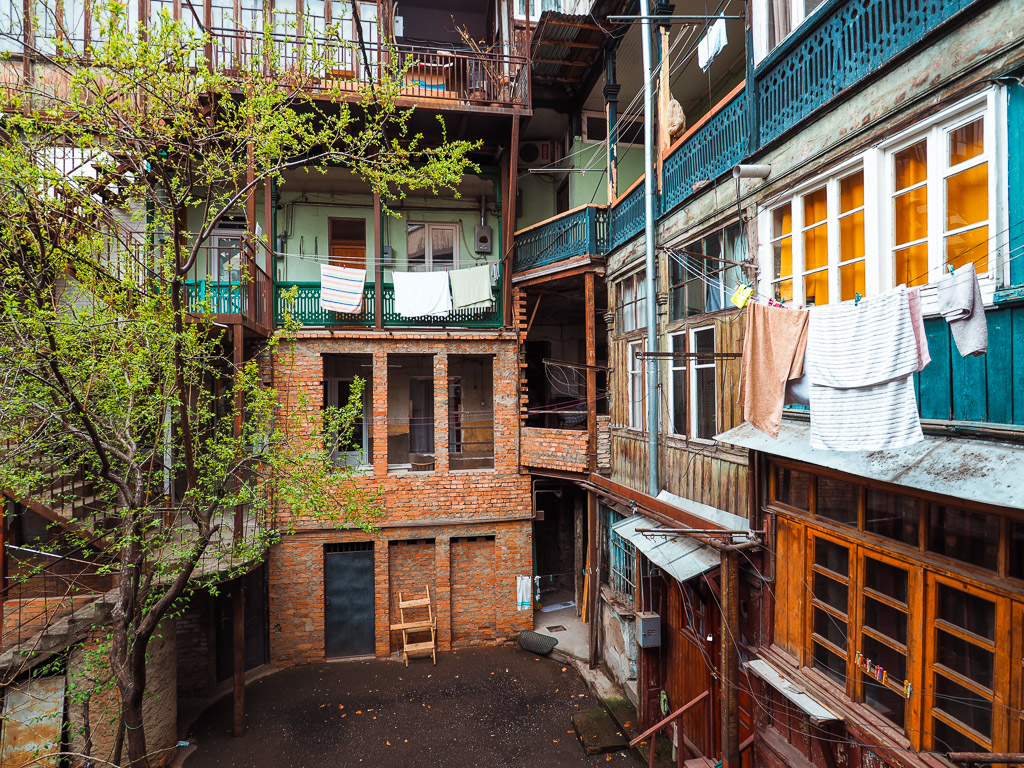 Emily-Lush-Tbilisi-courtyard. Always traveling? Or maybe you want to know more about the life of a travel blogger.