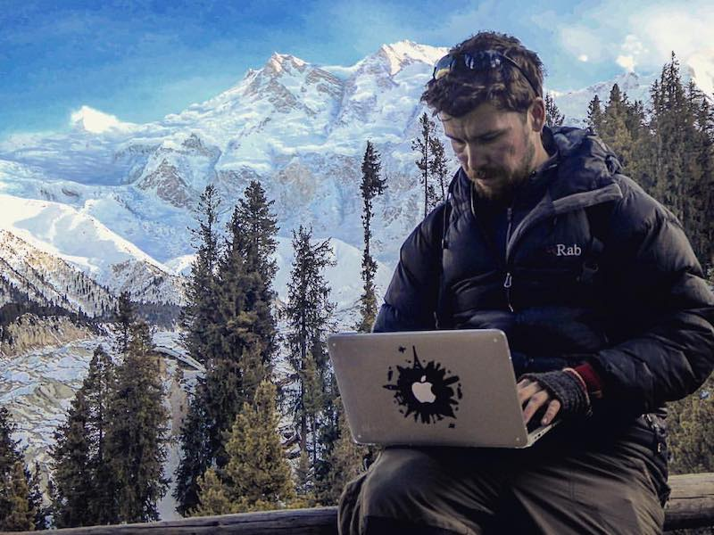 Long-travel pro Will Hatton working on his laptop with a backdrop of mountains and trees.