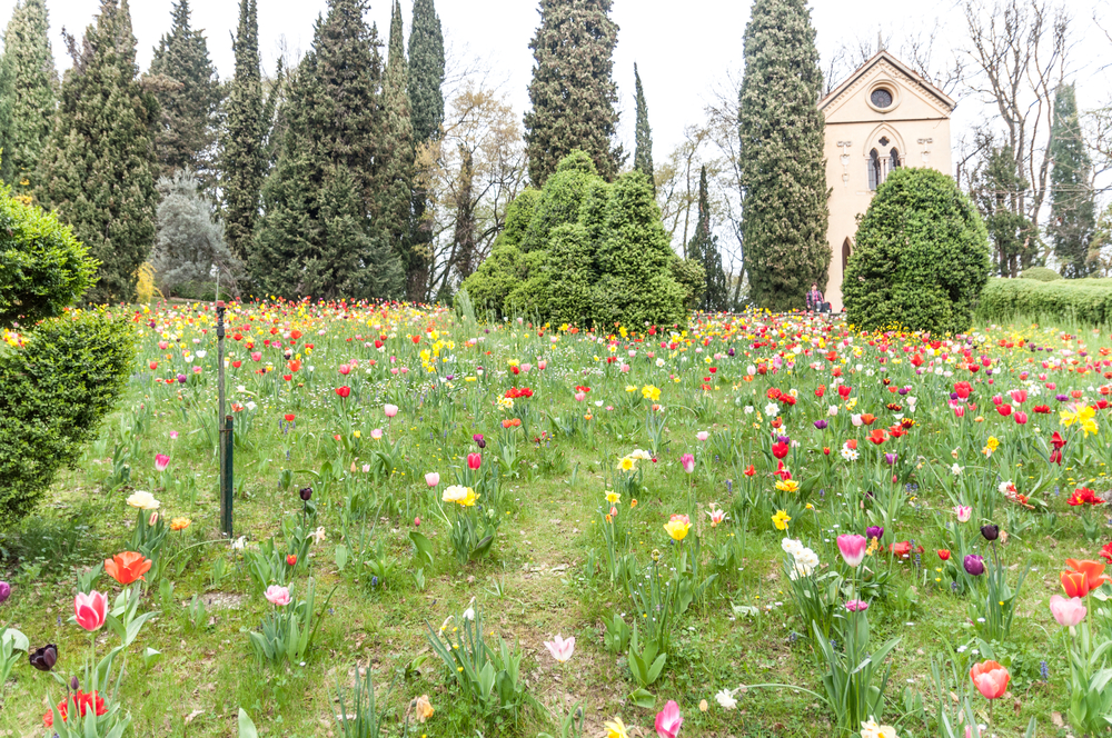 The hermitage at Parco Giardino Sigúrta, surrounded by poppies and vibrant wild flowers