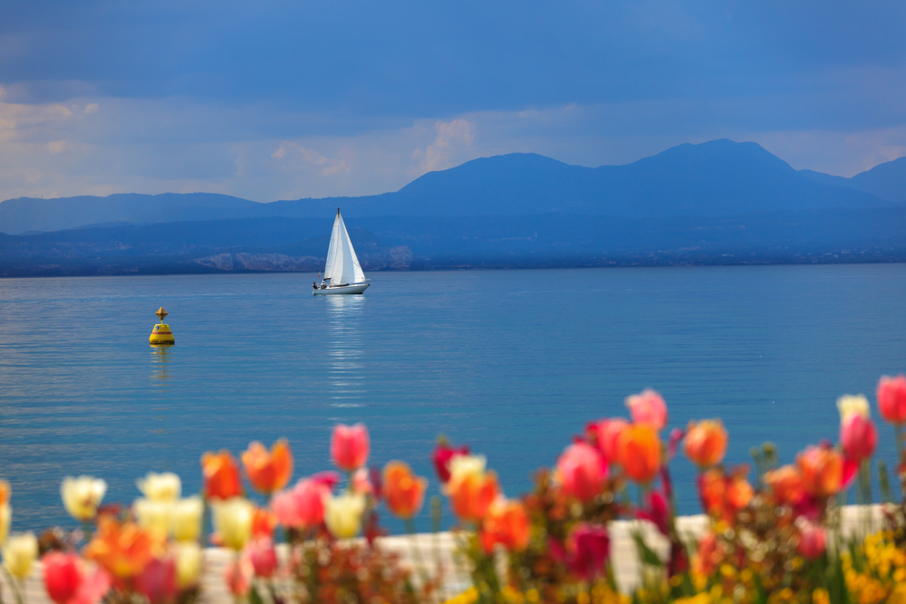 The serene beauty of Lake Garda flanked by tulip beds designed by Count Giuseppe Sigúrta.