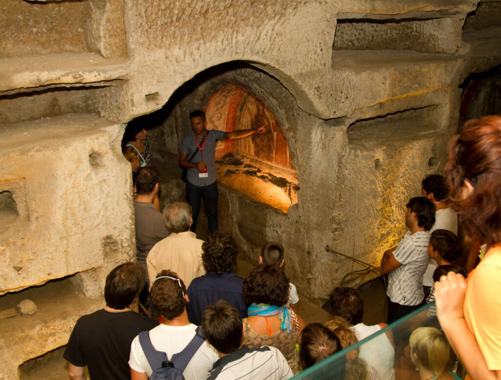 A guided tour in progress inside the Catacombs of San Gennaro.