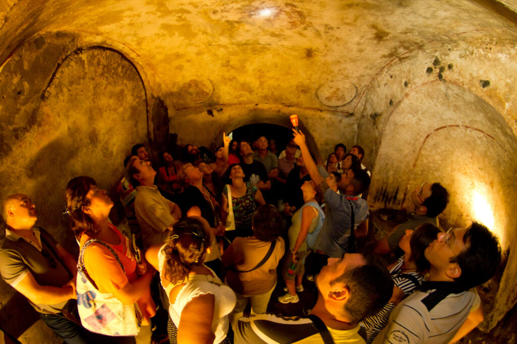A guided tour taking place within the catacombs of San Gennaro.