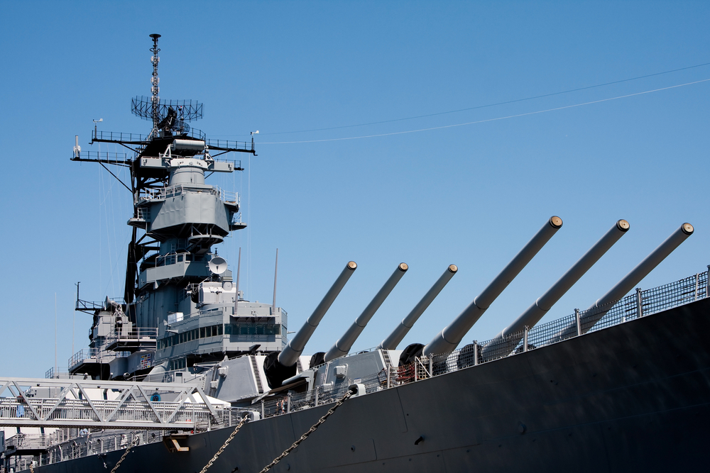 Battleship Iowa, a large naval ship featuring heavy cannons.