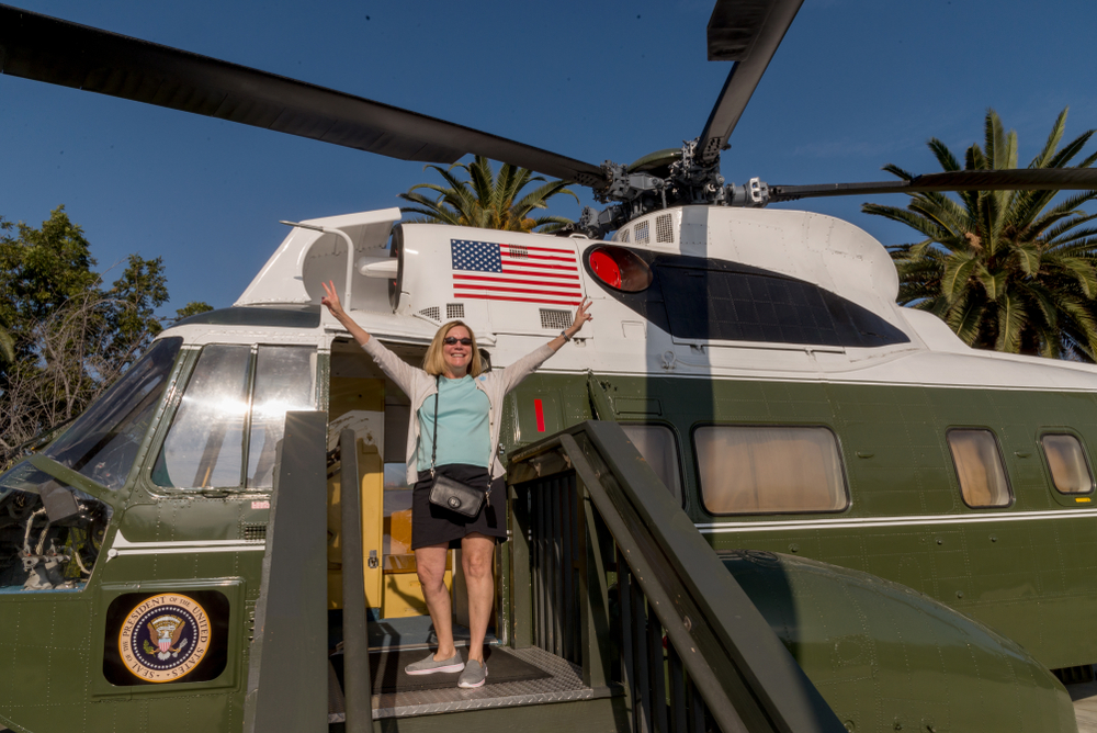 A woman posing in front of a helicopter found at the Richard Nixon Presidential Library and Museum, one of the top historical hidden gems in Los Angeles.