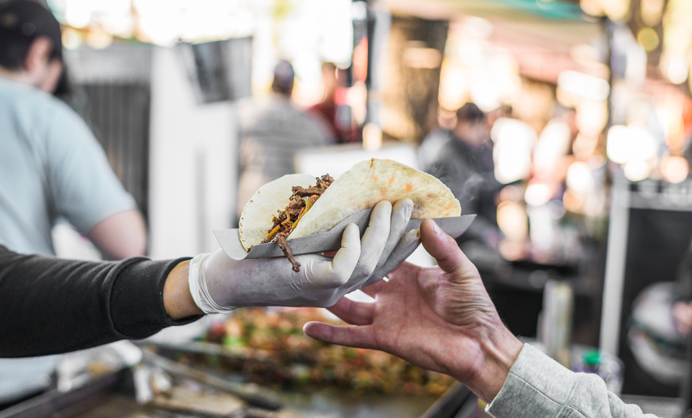 Tacos being handed over at a food market in Los Angeles.