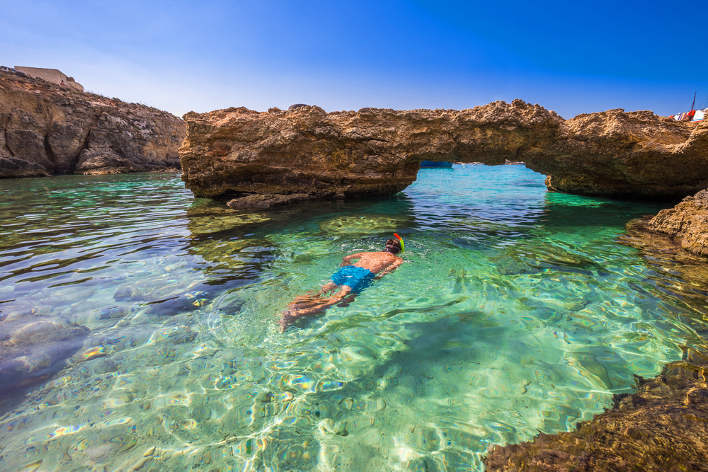An image of a man snorkeling around crystal-clear water in Comino.