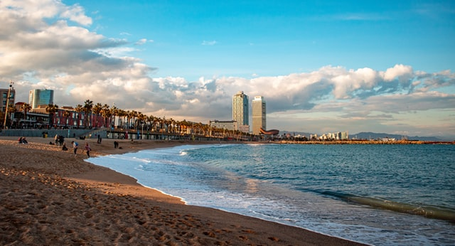 Barcelona's coastline showing a long stretch of beach and distant tower blocks