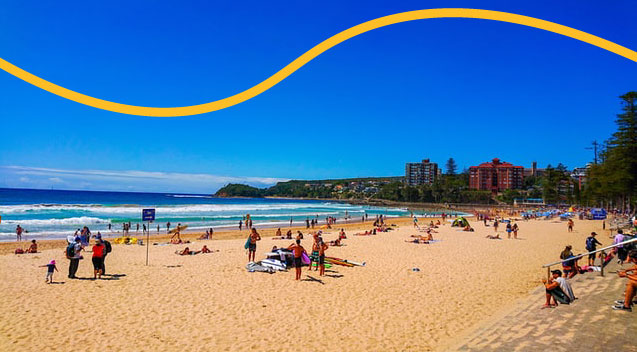 Sydney's Manly Beach showing golden sand, and blue sea and skies