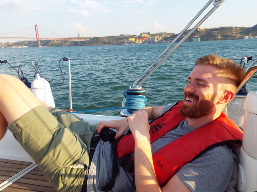 Bearded man in life jacket laughs  on yacht