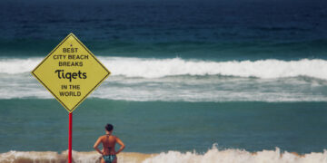 Woman in bikini looks out at waves with sign saying best city beach breaks in foreground