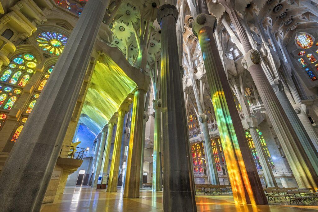 Rainbow-coloured light reflecting through the nave of the Sagrada Família.