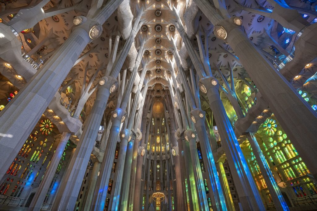 A view from inside the Sagrada Família, featuring multi-coloured light and high columns.