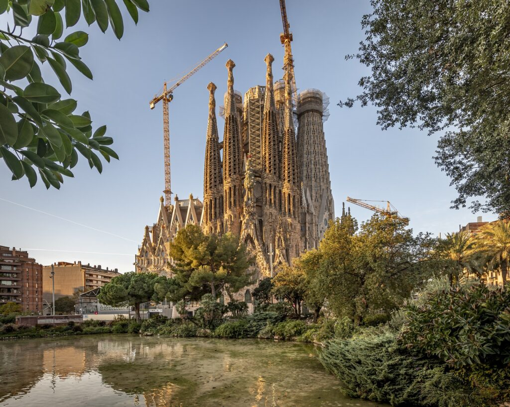 The exterior of the Sagrada Família in Barcelona, with a small park in the foreground.